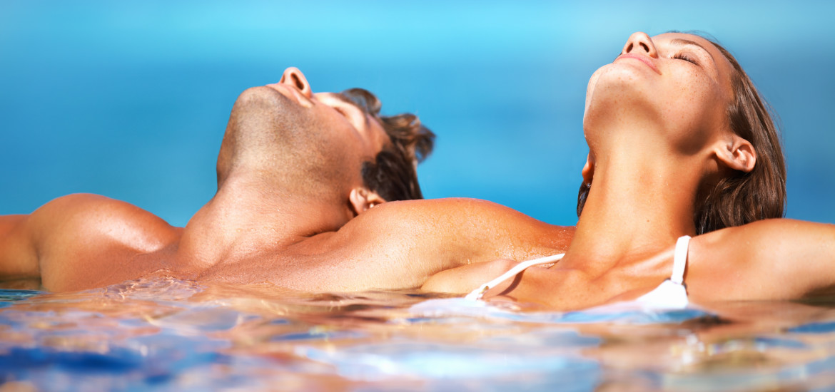 Young couple tanning while in a pool